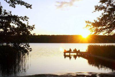 Paare auf dem Steg bei Sonnenuntergang